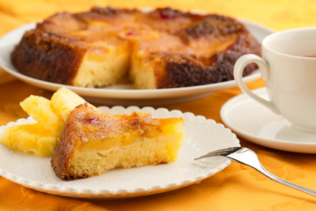 maraschino: pineapple cake and cup of tea on orange tablecloth
