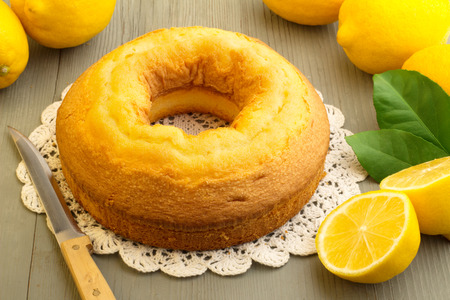 cake and yellow lemons on wooden board