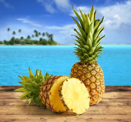 coctel de frutas: de piña en la mesa de madera en un paisaje tropical Foto de archivo