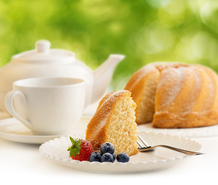slice of cake and tea in a blurry green background