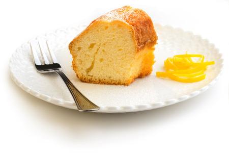 slice of cake garnished with lemon peel on white background photo