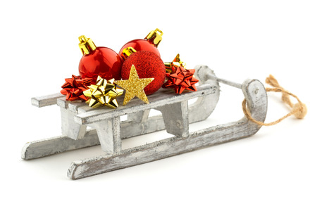 christmas baubles over a wooden sled isolated on white background photo