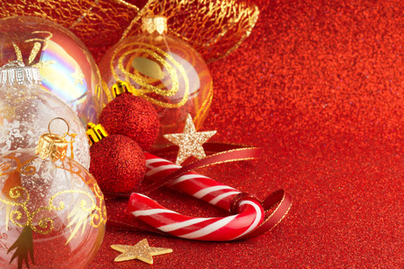 christmas balls, ribbons and candy cane on red background photo