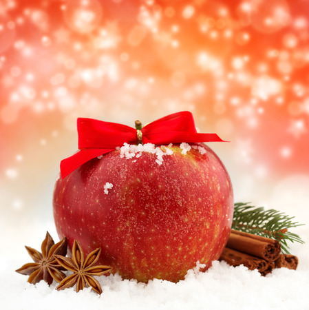 apple and cinnamon: apple with red ribbon and spices in the snow Stock Photo