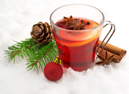 fir twig: mug of mulled wine and spices in snow
