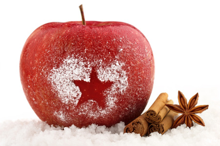 decorated red apple and spices in the snow Stockfoto