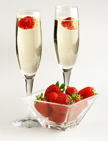 two champagne glasses and strawberries on white background