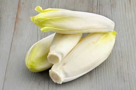 group of belgian endives on wooden table Stock Photo