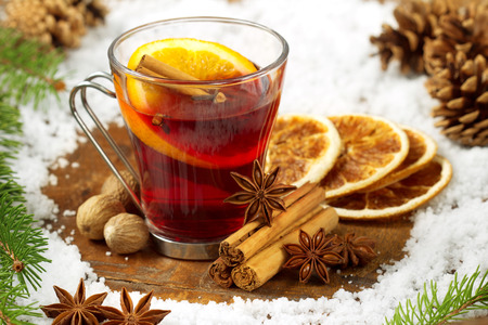glass of mulled wine, spices and snow on wooden table photo