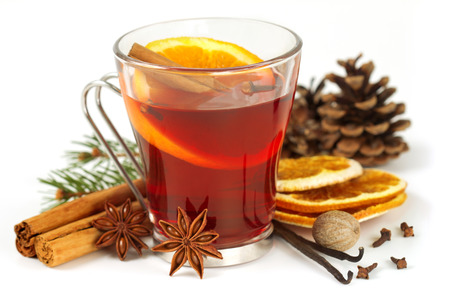 glass of mulled wine and spices on white background