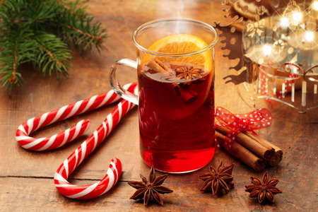 mulled wine and candy canes by candlelight on wooden table