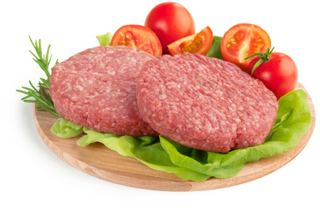 mincemeat: raw burgers, tomatoes and lettuce on wooden cutting board
