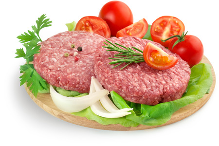raw burgers, tomatoes and lettuce on wooden cutting board