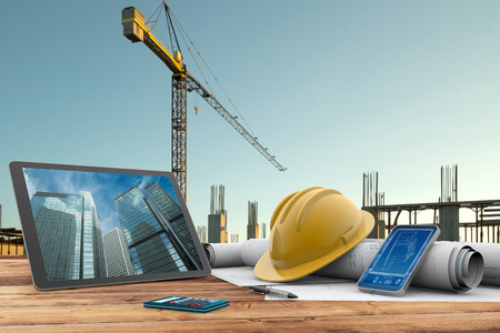 concrete construction: blueprints, safety helmet and computer in construction site