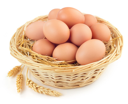 eggs in wicker basket and ears of wheat Stockfoto