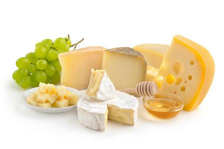 Wybór serów, miodu i winogron na białym tle
