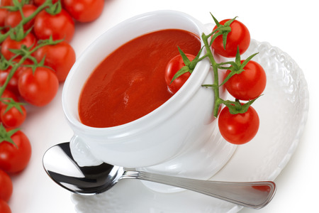 bowl of tomato soup and cherry tomatoes on white background photo