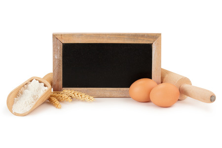 eggs, flour, wooden rolling pin and chalkboard photo