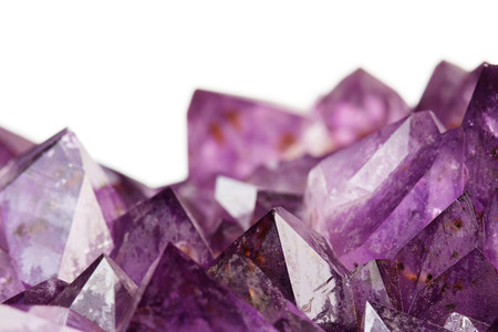 close up of amethyst crystals on white background