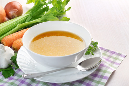 meat soup: bowl of broth and fresh vegetables on wooden table