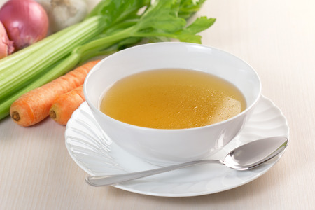 broth: bowl of broth and fresh vegetables on wooden table