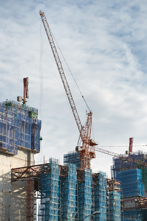 modern residential construction: cranes and scaffoldings in a construction site