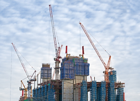modern buildings: cranes and scaffoldings in a construction site