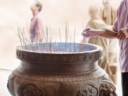 sticks of incense in a censer at the temple entrance photo