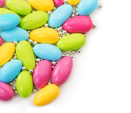 colorful sugared almonds and silver dragees on white background