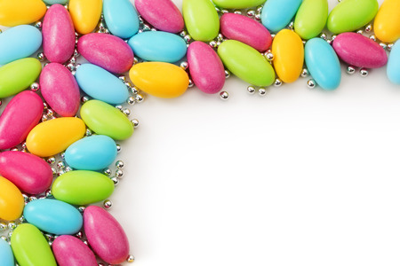 dragee: sugared almonds and silver spheres on white background