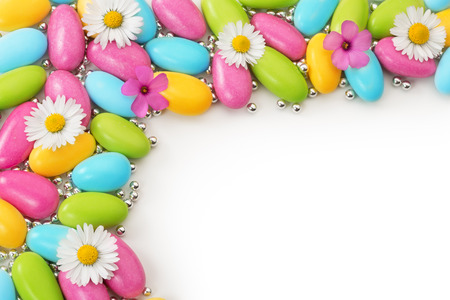 multicolored dragees and wildflowers on white background photo