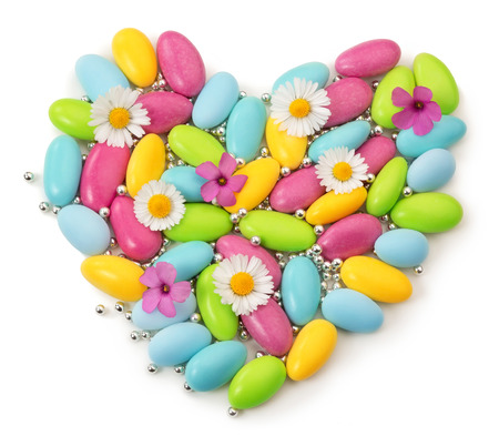 colorful dragees and wildflowers in shape of heart Stock Photo