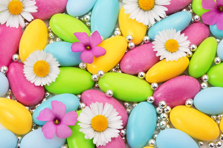heap of colored sugar coated almonds and wildflowers Stock Photo