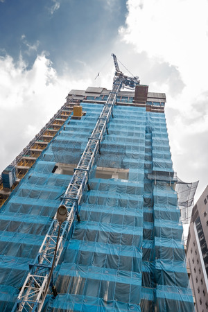 crane at work on scaffolds of tall building