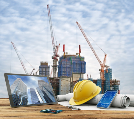 construction: blueprints and safety helmet over a table in construction site Stock Photo