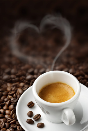 coffee cup over a heap of coffee beans