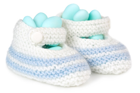 baby shoes: crochet baby booties filled with blue sugared almonds Stock Photo