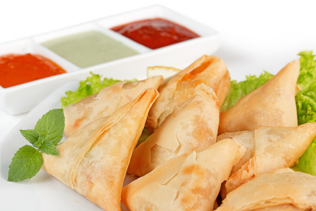 homemade fried samosas and sauces on white background photo