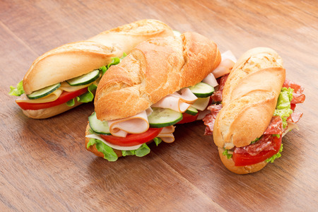 three sandwiches with savoury fillings on wooden table