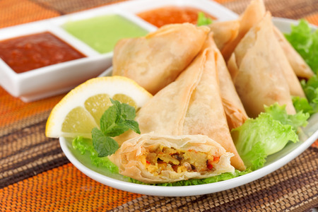 person appetizer: plate of vegetable samosa with indian sauces