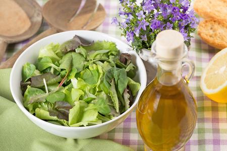 side salad: bowl of green salad, olive oil and lemon Stock Photo