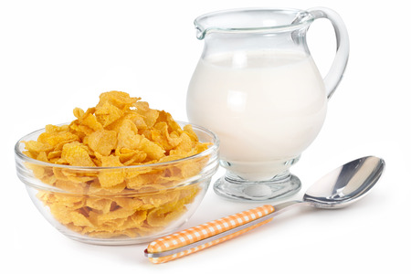 cornflakes, jug of milk and spoon isolated on white