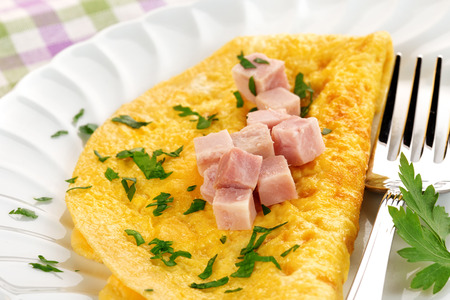 scrambled eggs: omelette garnished with diced ham and parsley