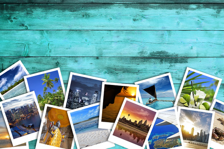 heap of travel photos on azure wood background Archivio Fotografico