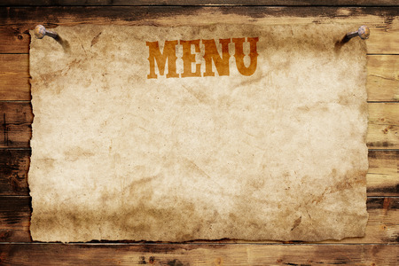 old menu card nailed on a wooden wall Stockfoto