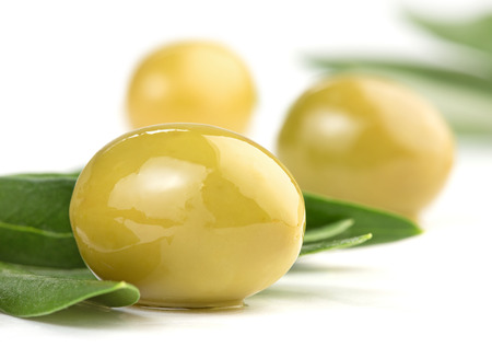olive green: close up of green olives and olive leaves isolated on white