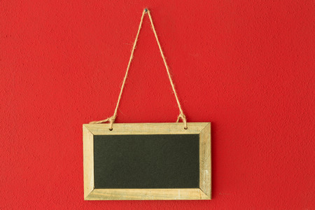 blank slate: blank chalkboard hanging on the red wall Stock Photo