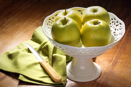 centerpiece: four green apples in a china centerpiece on wooden table