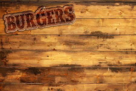 burger sign nailed to a wooden wall