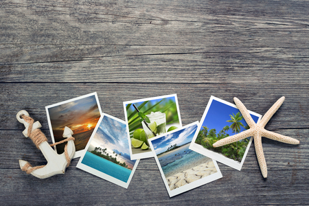 memories: seaside snapshots, anchor and starfish on wooden background Stock Photo